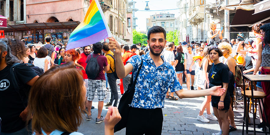 A young man standing in the street in Istanbul Turkey waving a pride flag. He is wearing a blue floral button down t-shirt.